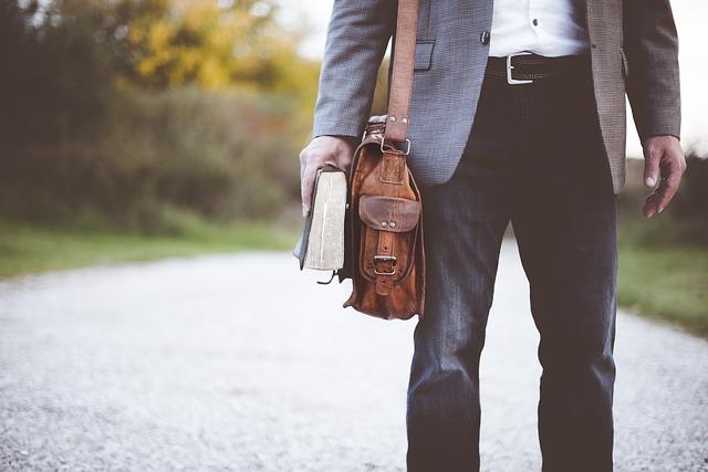 Muž s taškou cez rameno, ktorý drží v ruke knihu