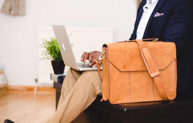Muž píšuci na notebooku, vedľa ktorého je položená kožená taška cez rameno