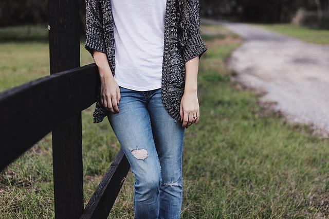 Žena v roztrhaných džínsoch a bielom tričku