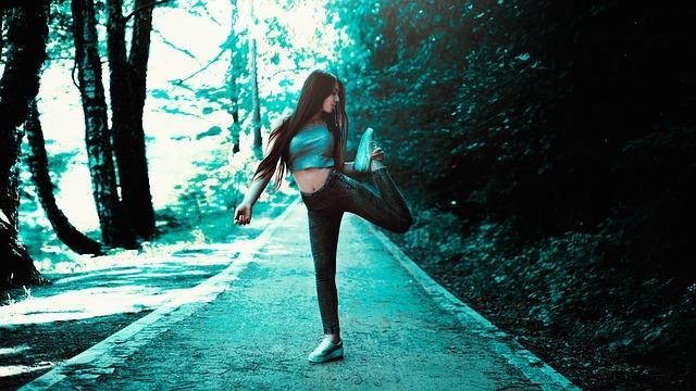 Žena na lesnej ceste v rifliach a sivom krátkom tričku
