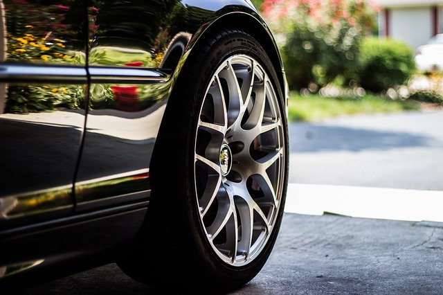 Koleso čierneho lesklého auta zaparkovaného v garáži