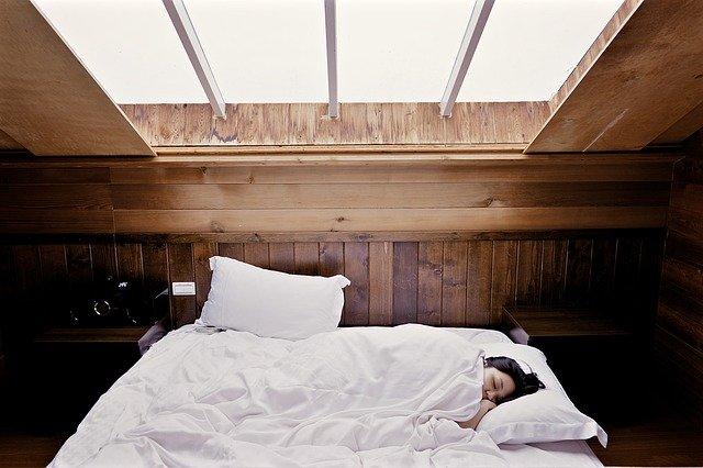 Žena spí v posteli v podkrovnej spálni